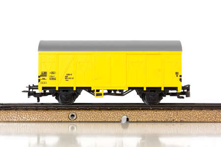 steam traction: Yellow boxcar of an electric model train on the rails