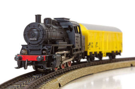 traction engine: Model electric freight train formed by a vintage steam locomotive and a yellow boxcar on the rails
