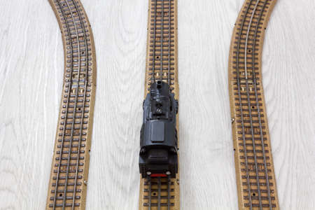 1950s vintage model steam locomotive on the rails over a wooden texture floor Stock Photo