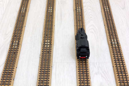 steam traction: 1950s vintage model steam locomotive on the rails over a wooden texture floor Stock Photo