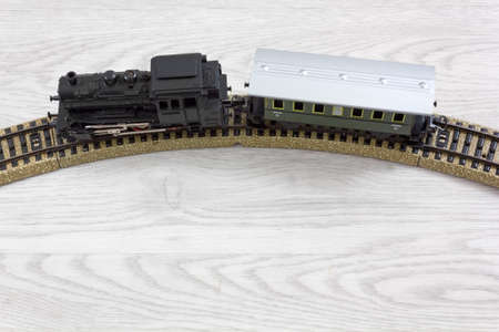 Model electric train formed by a vintage steam locomotive and a green passenger car on the rails over a wooden texture Stock Photo
