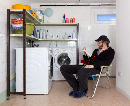 laundry room: Man reading a book while waiting for the laundry to wash in a home laundry room