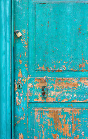 Old turquoise wooden door with peeling paint and rusty lock and handle