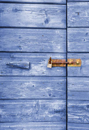 Old blue wooden door with peeling paint and rusty lock and handle