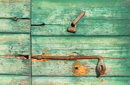 Close-up on an old green wooden door with peeling paint and rusty lock and handle
