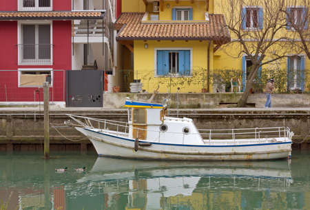 passerby: Moored small white boat in a canal with colored buildings in the background