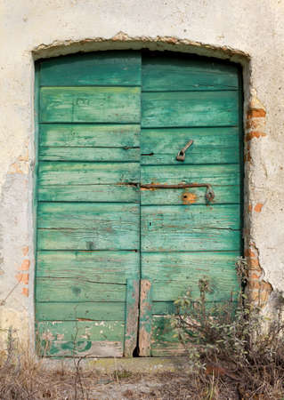 Old green wooden door with peeling paint and rusty lock and handle Stock Photo
