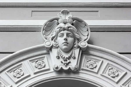 Art Nouveau marble sculpture of a feminine face on a building's exterior in Trieste, Italy