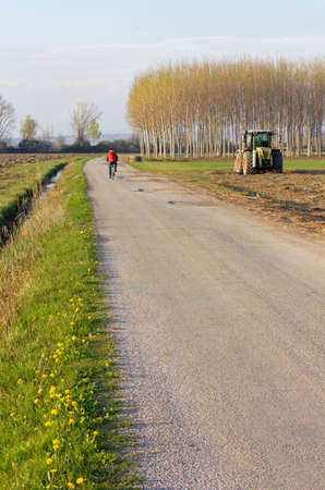 winter tires: Country road in an early spring afternoon with a cyclist in the background and a tractor at work in the field alongside