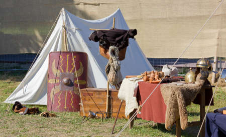 Tent in an ancient Roman encampment with war equipment and various utensils Stock Photo