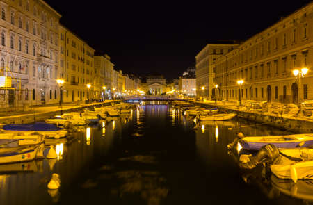 TRIESTE, Italy - August 3, 2017: Canal Grande and Piazza SantAntonio at night, with the neoclassic church of the same name in the background