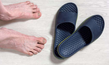 Male feet next to a pair of blue flip-flops on a white wooden floor