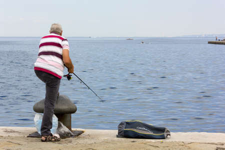 TRIESTE, Italy - June 23, 2014: Man seen from behind fishing from the citys seafront next to a bollard