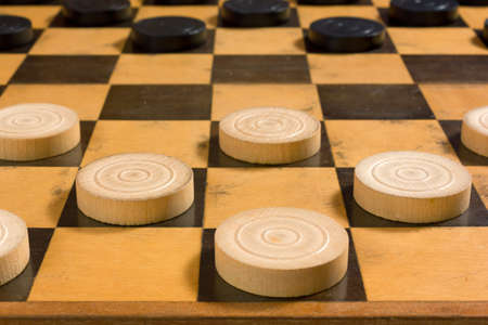 Black and white wooden pieces in the starting position on a checkerboard