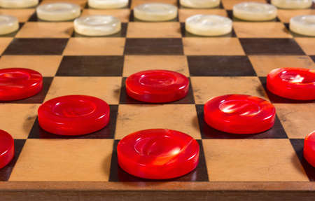 Red and white pearly pieces in the starting position on a checkerboard Stock Photo