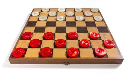 Altes Schachbrett auf einem weißen Hintergrund mit den roten und weißen perligen Stücken in der Ausgangsposition