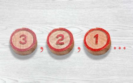 Drie cilindervormige houten stukken op een witte houten achtergrond met het aftellen van drie naar één Stockfoto