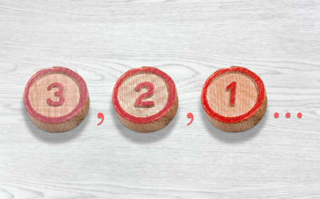 Three cylinder-shaped wooden pieces on a white wood background depicting the countdown from three to one Stock fotó
