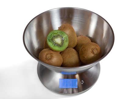 Modern electronic metal kitchen weighing scales with kiwi fruits