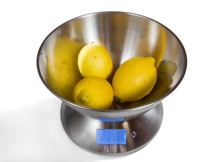 Modern electronic metal kitchen weighing scales with lemons Stock Photo