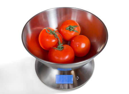 Modern electronic metal kitchen weighing scales with tomatoes