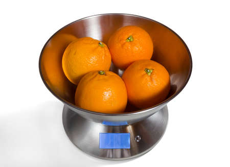 Modern electronic metal kitchen weighing scales with oranges Stock Photo