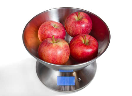 Modern electronic metal kitchen weighing scales with red apples