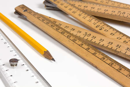 A measuring stick, a ruler and a pencil on a white background