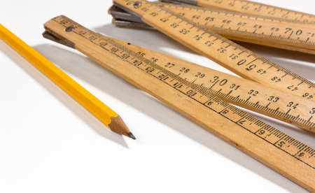 A measuring stick and a pencil on a white background Stockfoto