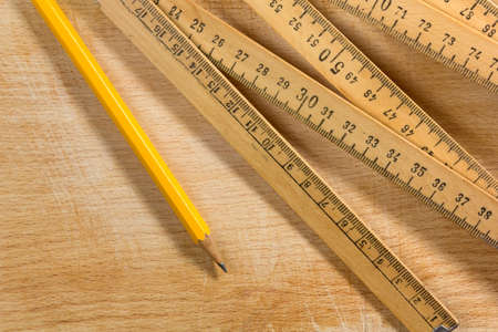 A measuring stick and a pencil on an old wooden table