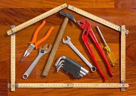 House shape folded measuring stick containing work tools Stock Photo