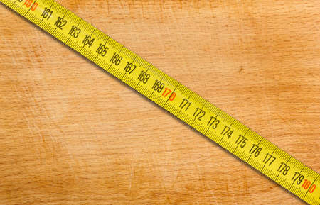 Segment of a yellow metal measuring tape placed diagonally on an old wooden table