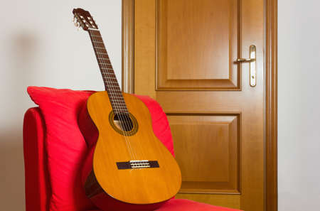 Classical guitar on a red easy chair with a wooden door in the background