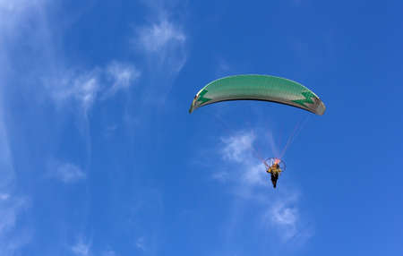 Powered paraglider flying in a clear blue sky