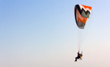 CAORLE, Italy - October 14, 2018: Powered paraglider flying in a clear sky