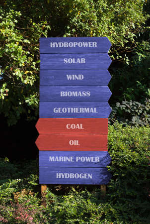 Block of nine wooden direction signs on a natural background, seven blue signs indicating the way to renewable sources and two red ones indicating not renewable sources