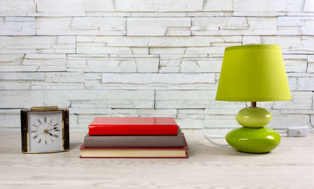 White wooden desk with a few books, a modern green lamp and a classic table clock