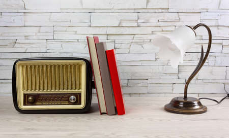 White wooden desk with a few books, a classic table lamp and a vintage radio tuner Reklamní fotografie - 123097365