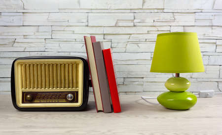 White wooden desk with a few books, a modern table lamp and a vintage radio tuner Reklamní fotografie - 123097364