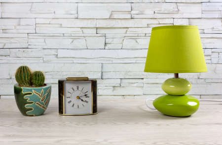 White wooden desk with a classic table clock, a modern green lamp and a small cactus Reklamní fotografie - 123097366