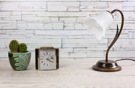 White wooden desk with a clock, a classic table lamp and a small cactus Reklamní fotografie - 123097367
