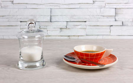 Orange colored cup of coffee with a modern design and a transparent sugar bowl on a white wooden table Reklamní fotografie - 123097368