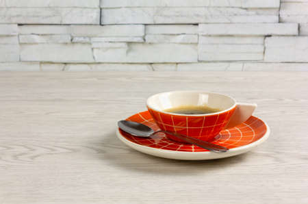 Orange colored cup of coffee with a modern design on a white wooden table, with a teaspoon on the saucer Reklamní fotografie - 123097369