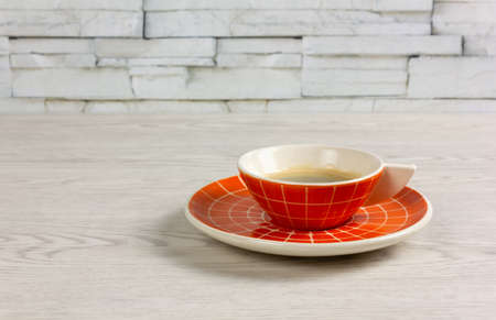 Orange colored cup of coffee with a modern design on a white wooden table Reklamní fotografie - 123097370