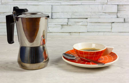 Orange colored cup of coffee with a modern design and a coffee maker on a white wooden table Reklamní fotografie - 123097376