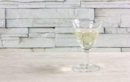 Stem glass half full of white wine on a white wooden table Reklamní fotografie - 123097379