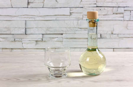 A small bottle on a wooden table, closed by a cork, full of white wine and next to an empty glass Reklamní fotografie - 123097382