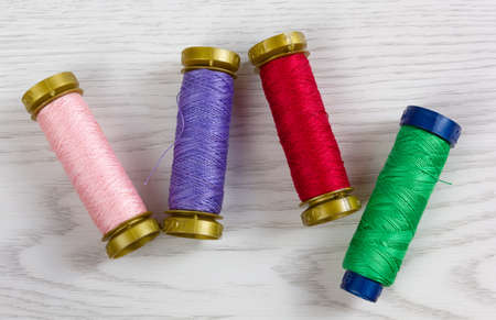Four thread spools of different colours on a white wooden background