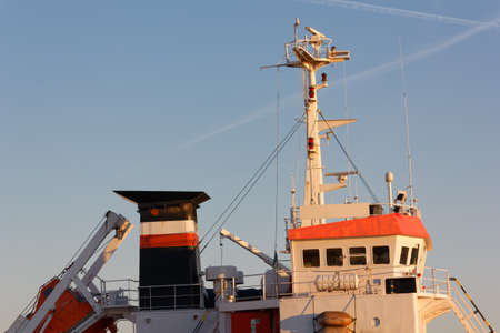 Bridge, mast and funnel of a bunkering vessel in the sunset light