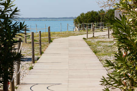 Perspective view of a boardwalk next to the beach in a seaside resort